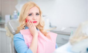 A woman experiences pain. Is it from the dental implants?